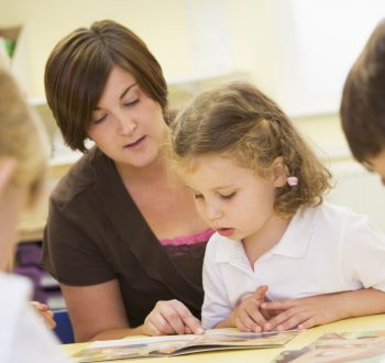 2127565-schoolchildren-and-their-teacher-reading-in-a-primary-class