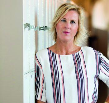 LR:s ordförande Åsa Fahlén lutar sig mot skåpen i en skolkorridor.