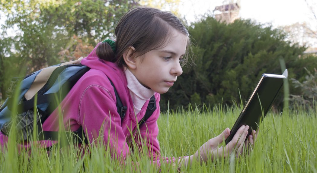 Teen girl reads electronic book laying on the grass