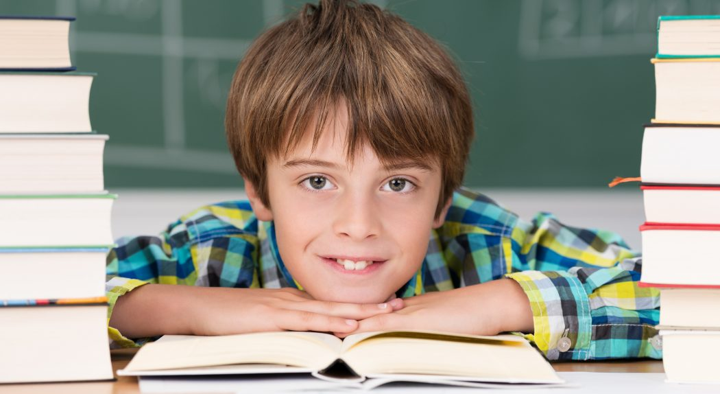 Young boy in school surrounded by textbooks