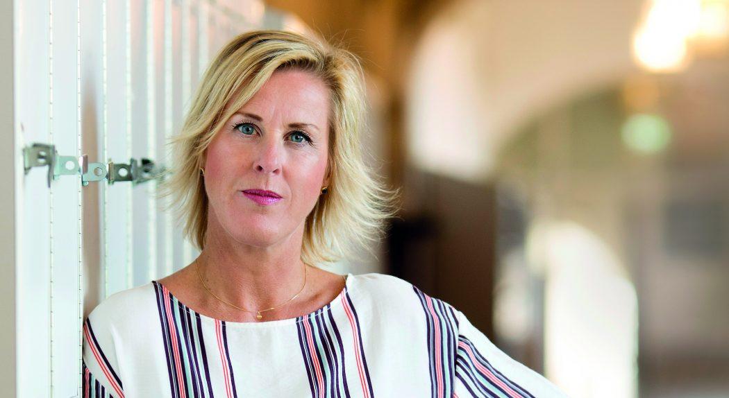 Åsa Fahlén lutar sig mot skåp i skolkorridoren.