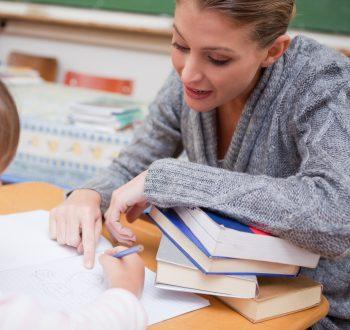 En lärare förklarar någonting för en elev i lägre ålder.