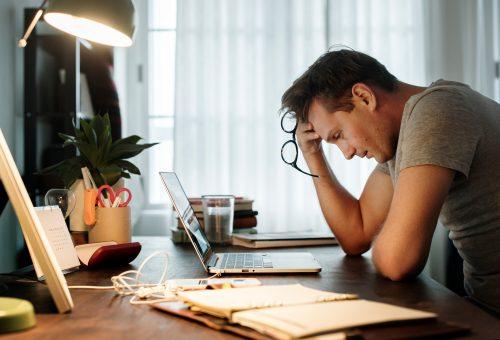 En trött man vid sitt skrivbord.