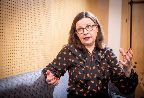 Anna Ekström sitter i en soffa, pratar och gestikulerar.