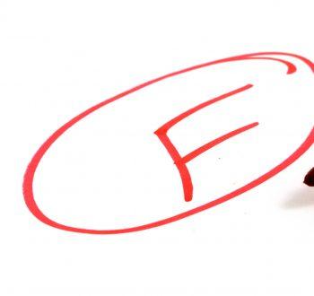 """En röd penna och betyget """"F"""" skrivet i en cirkel."""
