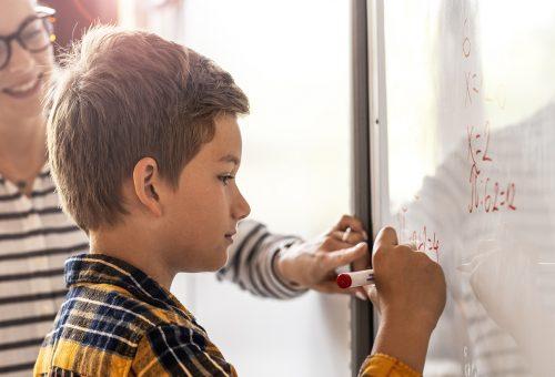 Lärare och elev räknar på tavlan.