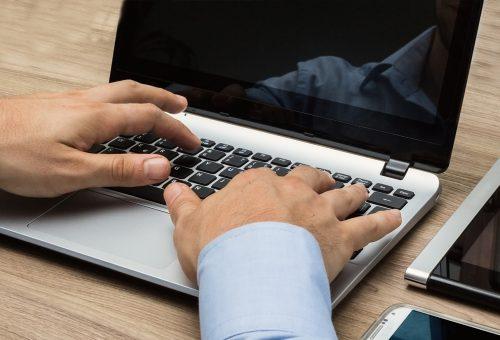Man sitter vid dator och skriver.