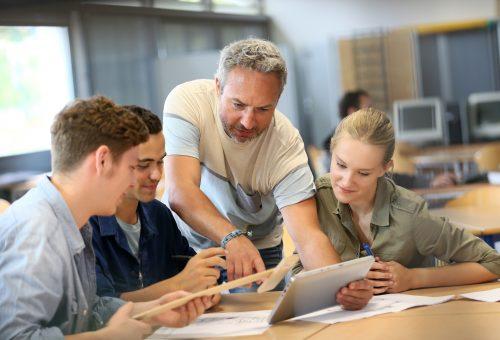 En lärare instruerar sittande elever.