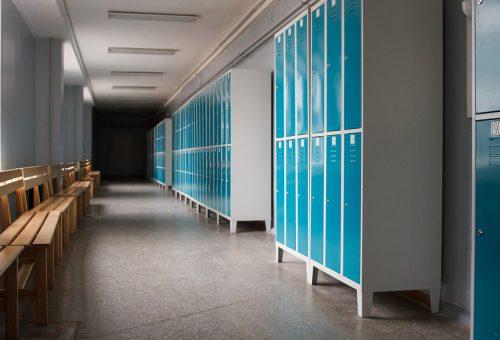 Skolkorridor med skåp och bänkar.