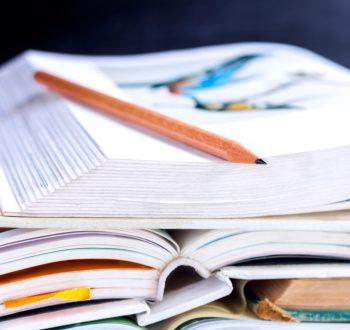 Läromedel, böcker på hög, penna