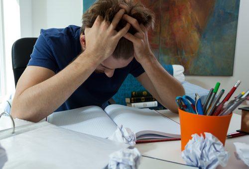 Trött student som pluggar hemifrån.