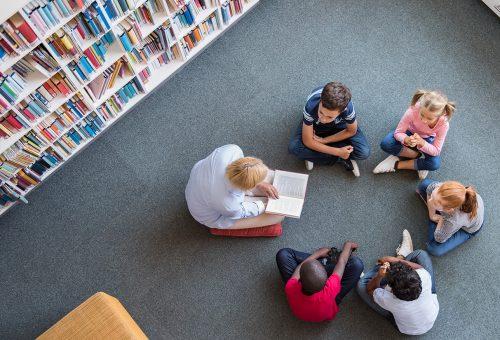 Skolbibliotekarie och elever som läser
