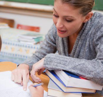 Lärare visar elev i bok